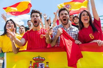 Spanish supporters cheering at stadium with flags