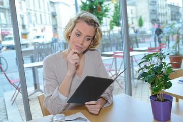 woman looking at menu for ordering food in restaurant
