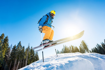 Low angle shot of a skier jumping in the air while skiing in the mountains copyspace. Blue sky, sun and winter forest on the background