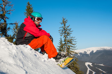 Shot of a snowboarder enjoying terrific view of snowy mountains relaxing on the edge of a slope looking around copyspace recreation travelling tourism