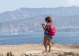 Girl shooting Sorrento's coast at Bagni della Regina Giovanna. Naples_Italy