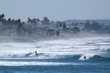Surfers cool off in the waves during a Southern California heat wave in Oceanside, California