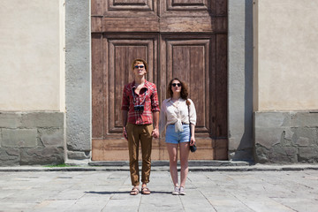 Young Couple Standing In Front of a Church Gate in Piazza Santo Spirito Florence. Tuscany Italy