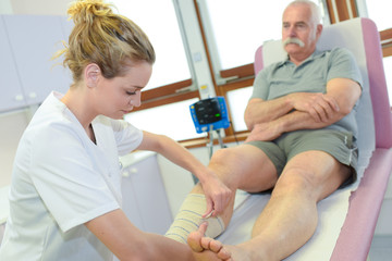 senior male patient cured by female physiotherapist