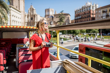 Young happy woman tourist in red dress having excursion in the open touristic bus in Valencia city, Spain Wall mural