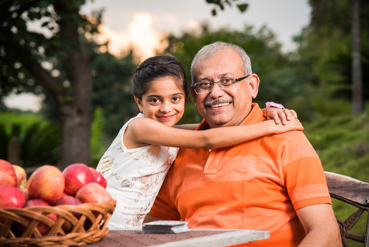 Young Indian girl embracing grandfather sitting in garden, Portrait of Indian grandfather and Grandchild