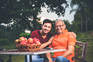 Indian father with handsome son. Portrait of Indian young adult son embracing father, sitting outdoor in lawn