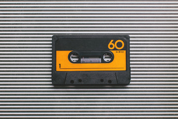 Yellow and black cassette tape on striped background.