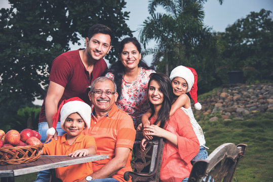 Indian family celebrating christmas and posing for a group photo. Three generations of indian family having fun on xmas wearing christmas hats or santa hats, sitting outdoors, selective focus