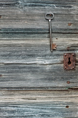 Grunge wooden door with rusty keyhole and key