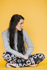 Young fashion girl sitting on yellow background