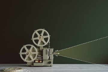 Old movie projector in front of the chalkboard with drawn light beam