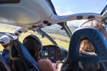 Three people in a helicopter cabin in mid flight over Kauai, Hawaii