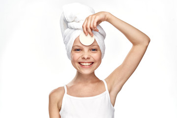 beauty, little girl with a towel on her head in her hand a cotton disc on an isolating background, smile