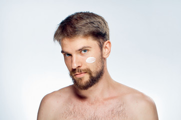 beautiful man with beard on face cream skin care on light background portrait