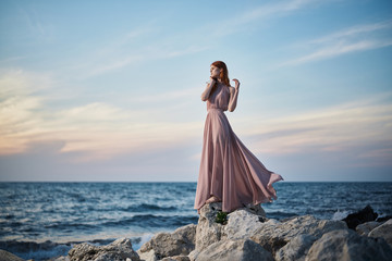 beautiful woman in a dress on the coast by the sea, nature