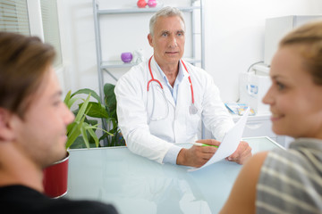 Doctor giving good news to young couple