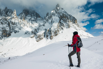 Young woman explorer looking at the mountain range in winter scenery