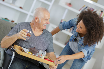 positive woman takign care of her ill grandfather
