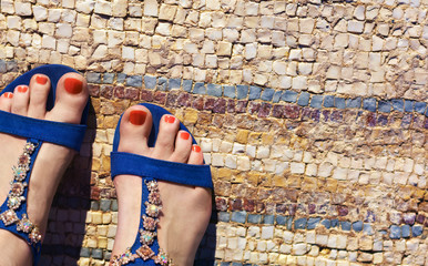Pedicure girl feet in blue sandals with gems standing on antique mosaic