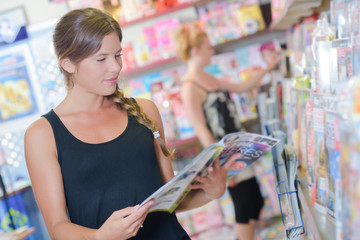 Lady browsing magazines in a newsagents