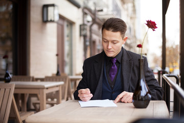 A wealthy young businessman looks through a business contract at lunchtime.