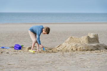 Boy building a sand castle on the beach