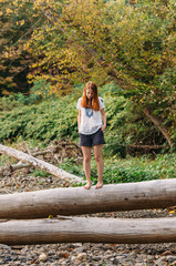 girl on fallen tree over a creek in autumn