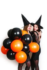Two happy sexy women in black witch halloween costumes with orange and black balloon on party over white background