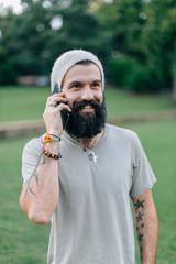 Tattooed man with a big beard talking on the phone
