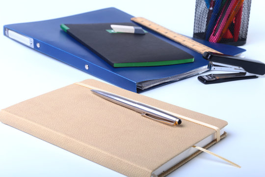 Colorful notebooks and office supplies on white table.