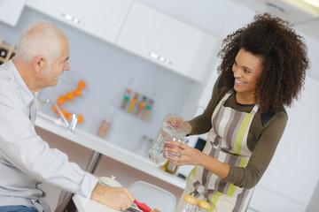 smiling home carer serving meal to elderly man