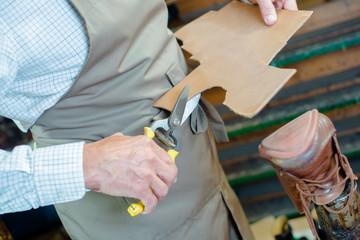 cobbler cutting cardboard