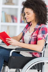 young female reading on wheelchair