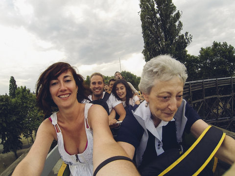Woman taking a self photo of herself and family on the top of a roller coaster