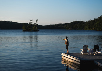 Man fishes on a lake at sunset on a summer night