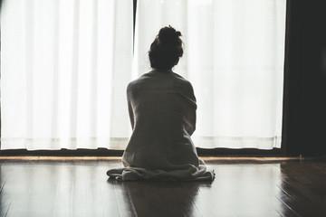 部屋の窓際に座っている寂しい女性