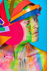 Model with colorful abstract makeup in multicolored helmet