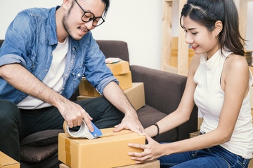 Young asian man and woman taping up a cardboard box in the office SME business, relocation and new small business concept, SME concept