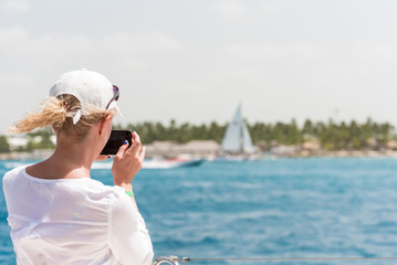 Woman in white on the deck of a yacht, Saona island, Dominican Republic. Copy space for text.