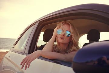 Blonde female with sunglasses looks through car window sitting on passenger seat