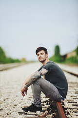 Young urban man sitting on the railroad