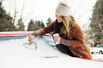 Young woman draws heart on windshield of car in winter