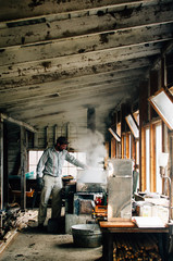 man tending maple syrup inside his sugar shack