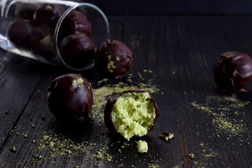 Healthy raw energy bites with coconut, avocado and tea matcha. Vegan chocolate truffles on dark wooden background. Homemade candy. Copy space