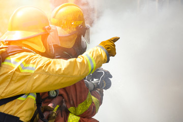 two firefighters water spray by high pressure nozzle to fire surround by smoke with flare and copy space
