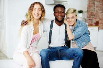Happy young African-american man embracing his two affectionate girlfriends