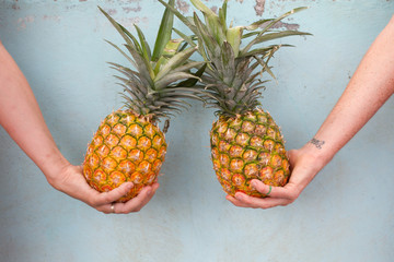 Arms holding two tropical pineapples