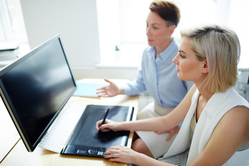 Young designer listening to her colleague advice while retouching images in front of computer