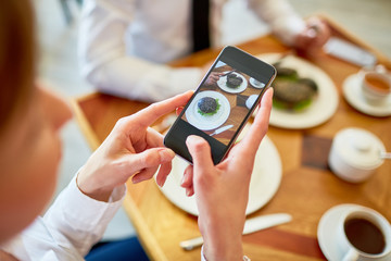 Close-up shot of unrecognizable woman taking photo of appetizing burger while having lunch at modern cafe, focus on foreground